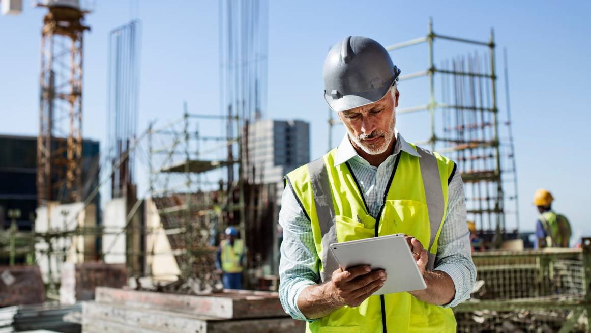 facility manager reading notes on the tablet at the construction site
