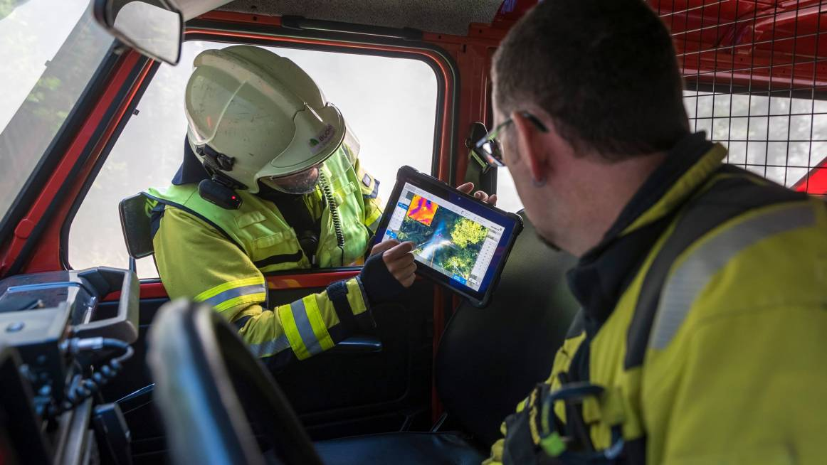 firefighter is pointing to the tethered drone footage on his command tablet during forest fire mission